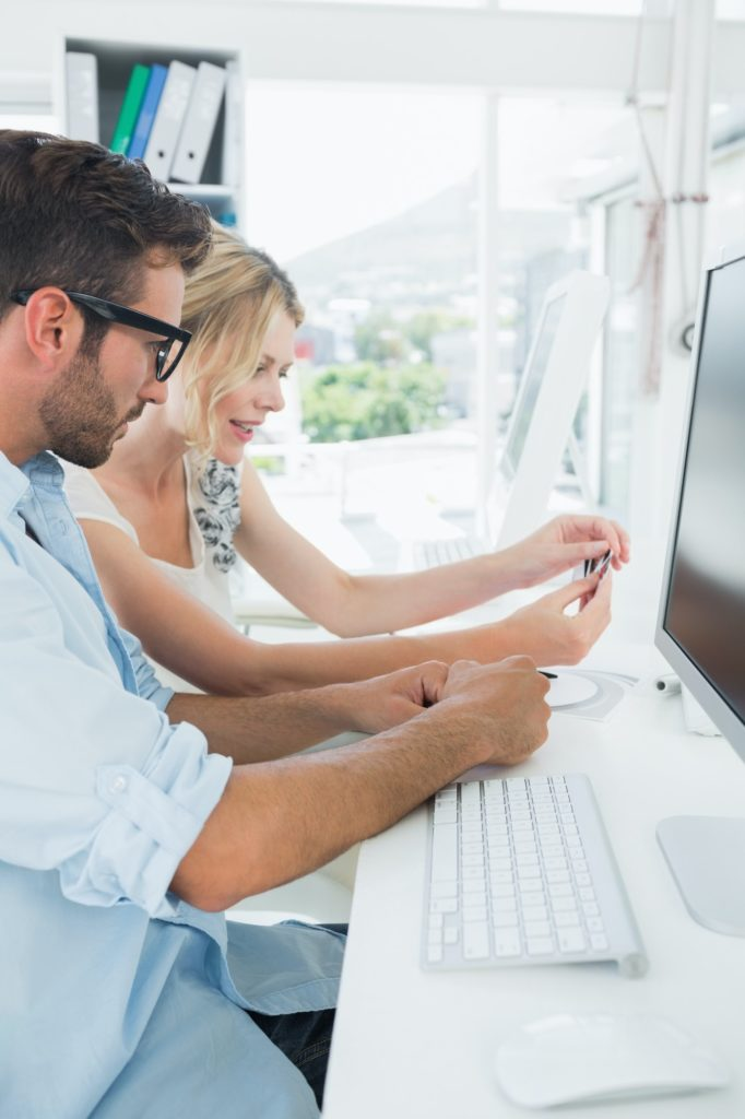 Side view of smiling casual young couple working on computer in a bright office